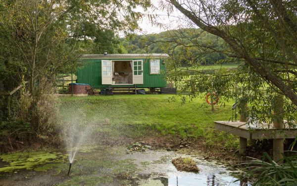 Shepherd's hut with hot tub and a pond